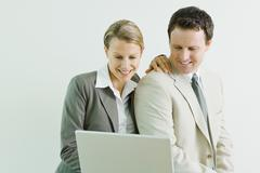 Male and female business associates using laptop computer together, both smiling - stock photo