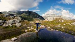 water reflection of man standing in front of mountain lake - stock footage