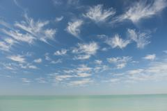 Wispy clouds over tranquil sea - stock photo