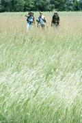Hikers walking through field Stock Photos