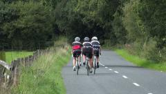 Zoom, cyclists bike along road in trough of bowland, lancashire, england Stock Footage