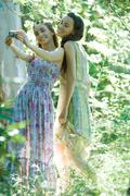Two young women wearing sundresses, standing in forest, taking photo of selves Stock Photos