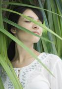 Stock Photo of Woman standing in lush foliage, eyes closed, smiling