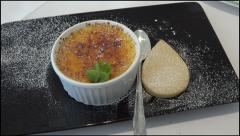 Dessert of creme brule with shortbread biscuit on black plate Stock Footage
