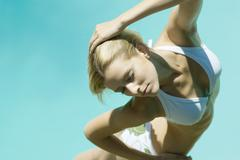 Young woman standing in bikini with hand behind head, eyes closed, high angle Stock Photos