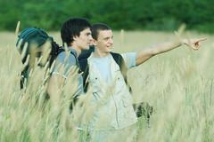 Two hikers standing in field, one pointing out of frame Stock Photos