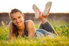 young smiling woman resting after exercising - stock photo