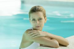 Woman wearing halter bathing suit, head and shoulders, leaning on edge of pool Stock Photos