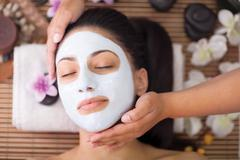Spa therapy for young woman having facial mask at beauty salon Stock Photos