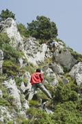 Hikers climbing rocks, rear view - stock photo