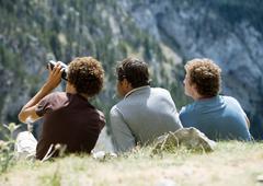Three men looking at mountain view, one using binoculars Stock Photos