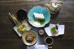 Japanese meal with various tofu dishes and tempura vegetables, overhead view - stock photo