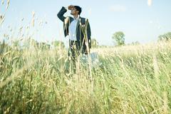 Businessman walking through field, shading eyes - stock photo