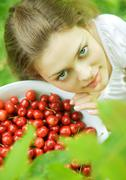 Woman holding bowl of cherries, smiling at camera - stock photo