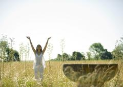 Woman standing in sun salutation pose, in field Stock Photos