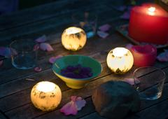 Candles glowing on table decorated with rose petals, and bowl holding floating Stock Photos