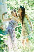 Two young women wearing sun dresses, standing in forest, taking photo with Stock Photos