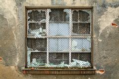 Broken window in an old industrial building - stock photo