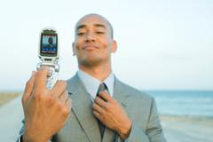 Businessman photographing self with cell phone at the beach, smiling, adjusting Stock Photos