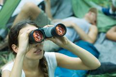 Woman looking through binoculars, hiking companions resting in background - stock photo