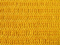 Crochet pattern from single and triple crochet stitch in yellow - stock photo