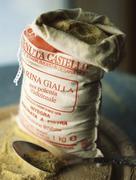 Stock Photo of Open sack of polenta corn meal with metal scoop