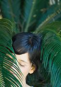 Woman standing amongst leaves, head and shoulders Stock Photos