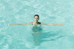 Young woman in pool with arms out and eyes closed - stock photo