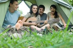 Friends in tent together, teen girl playing guitar - stock photo