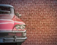 Classic car against red brick wall Kuvituskuvat
