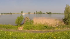 Vehicle shot downstream along River Lek and floodplains + rhine barge Stock Footage
