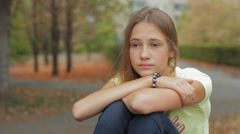 Sad And Unhappy Teenage Girl Sitting Alone In Autumn City Park HD Stock Footage