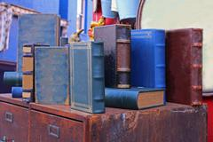 Old used books in hard cover sold on vintage market Stock Photos