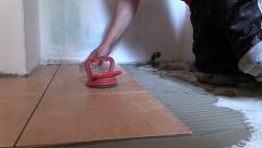 Worker man place floor tiles. Home renovation. Right side slide Stock Footage