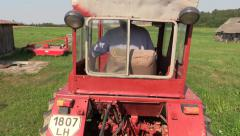 Farmer drive red old tractor between farm building and equipment Stock Footage