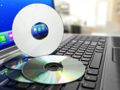 Software cd on laptop keyboard. compact disks. Stock Illustration