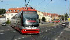 Passing trams on the urban street - cars - buildings - nature (trees) - sunny Stock Footage