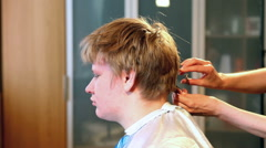 The hairdresser does a hairstyle to the client - young man Stock Footage