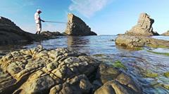 Dolly shot of fisherman fishing on paradise Sea coast - stock footage