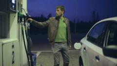 Filling station. A man fills his car with gasoline at night - stock footage