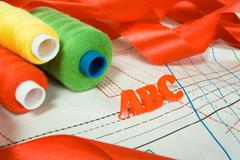 sewing tailor school concept, abc letters, threads and red ribbon - stock photo