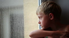 Alone little boy looks raindrops through window glass - stock footage