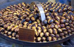 roasting chestnuts on the grill by a street vendor in rome - stock photo