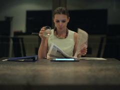 Businesswoman reading newspaper and drinking in the offcie at night NTSC Stock Footage