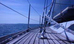 the curved teak deck of a yacht sailing at sea - stock photo