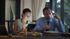 Business couple with cellphone, tablet computer and laptop eating dinner HD Stock Footage