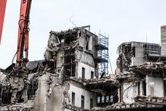 Building demolition by machinery for new construction. Stock Photos