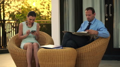 Business couple listening to music and reading newspaper on terrace HD Stock Footage