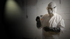 Hazmat doctor looking at a sample - stock footage