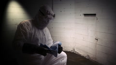 Hazmat doctor putting sheet over dead person Stock Footage